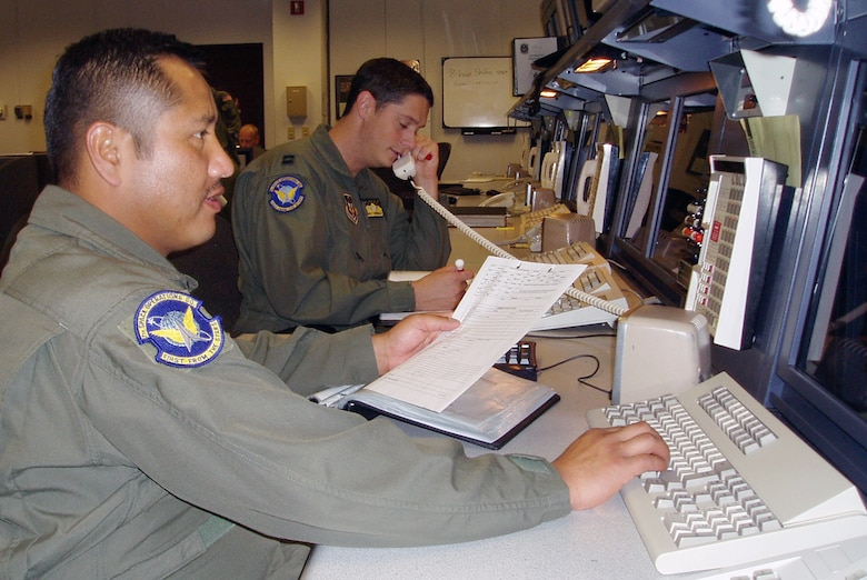 Tech. Sgt. Juan Gutierrez, left, and Capt. Garrett Donnelly of the 7th Space Operations Squadron at Schriever Air Force Base, Colo., check on the status of a satellite to ensure it is operating within normal parameters. The reservists are among the more than 700 members of the 310th Space Group. The group will become a space wing March 7 as its mission grows to meet the Air Force's expanding role in space. (U.S. Air Force photo)
