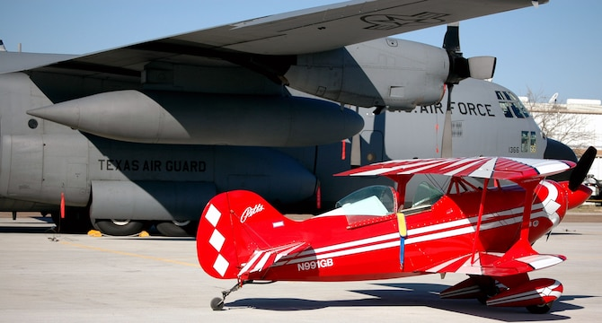 A small but colorful aerobatic biplane contrasts with the venerable gray C-130 aircraft of the 136th Airlift Wing, from Fort Worth, Texas. (Texas Military Forces photos by Spec. Jennifer Atkinson)