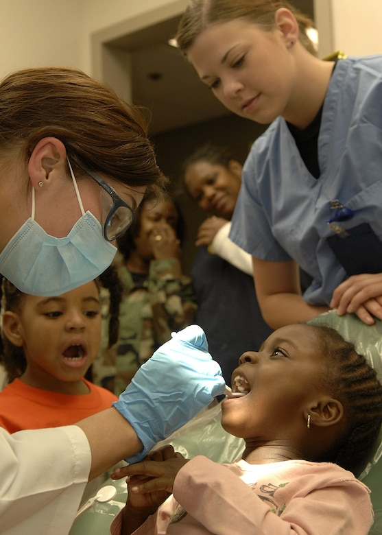 Capt. Sara Hale, 61st Medical Group, takes a look at three year old Nia Adeogun's teeth during Dental Awareness Week at the base dental clinic, Feb. 27. (Photo by Stephen Schester)