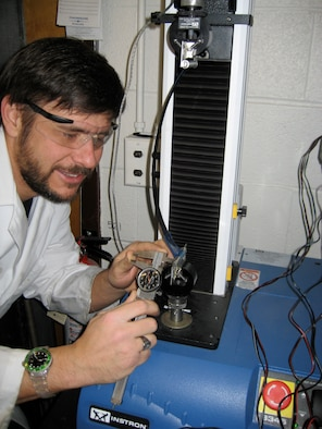 Dr. Barrett-Gonzalez checks lateral clearance on an adaptive missile fin flight control actuator during a blocked force and deflection test. (Photo provided)