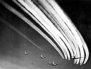B-17 vapor trails fill the sky as a flight of B-17s join with other flights for a long range mission.