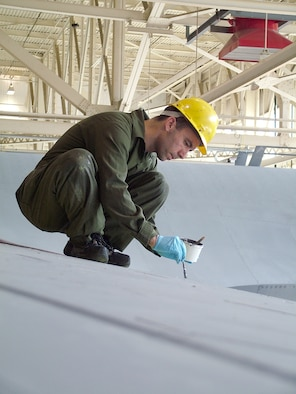 WESTOVER AIR RESERVE BASE, Mass ? TSgt. Christopher W. Davis a Sheet Metal Specialist in the Isochronal (ISO)Dock, works on replacing a damaged section of a C-5?s wing while below three Airman from the 445th Airlift Wing, Wright-Patterson Air Force Base, Ohio work on securing the sheet metal section from the inside of the wing. The Ohio Airman are here for a few weeks for training on the C-5 airframe by the Westover maintainers, while their unit makes the conversion from C-141s to the C-5 Galaxy. This is the first C-5 to be put through the rigorous Westover inspection under the new label of Regional ISO Center.