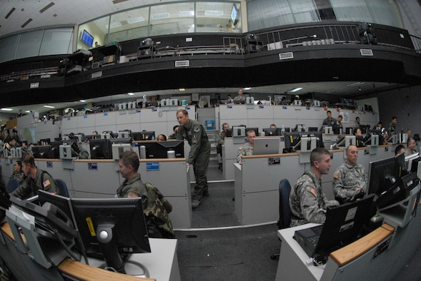 """OSAN AIR BASE, Republic of Korea – Col. Rob Kyrouac, (center), 607th Air and Space Operations Center chief of combat operations division, leads members on the """"pit floor"""" of the Korean Air Operations Center during Exercise Key Resolve March 5. Key Resolve is an """"operational-level,"""" Republic of Korea-U.S. training exercise held peninsula-wide to ensure """"operational"""" readiness of air, space and cyberspace operations in the Korean theater of operations. This annual exercise is held in conjunction with Foal Eagle 2008. Both exercises demonstrate U.S. resolve to support the Republic of Korea against external aggression while improving ROK/U.S. combat readiness and joint/combined interoperability. (U.S. Air Force photo/Staff Sgt. Lakisha Croley)"""