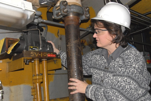 Kim Luther, an Aerospace Testing Alliance Test Operations systems engineer for the center's 16-foot transonic wind tunnel, inspects a 16T High Angle Automated Sting (HAAS) pitch blocking valve. She is in the process of completing a job that replaced four of these valves due to performance issues. The valves have been in place for more than 20 years and had never been removed, rebuilt or replaced. (Photo by David Housch)