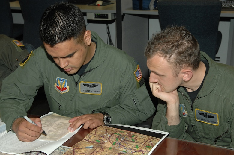 Airman 1st Class Jorge Jimenez, left, and Staff Sgt. Matthew Shumaker, 79th Rescue Squadron, review mission plans at the 79th RQS here Feb. 27. (U.S. Air Force photo by Airman 1st Class Noah R. Johnson)