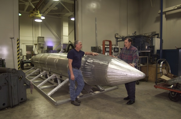 Al Weimorts (left), the creator of the GBU-43/B Massive Ordnance Air Blast bomb, and Joseph Fellenz, lead model maker, look over the prototype before it was painted and tested. (Courtesy photo)