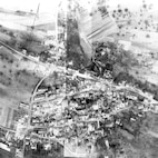 Ninth AF 2nd Phase Interpretation Report US10/D 734  LOCALITY:  HUNDSBACH ESPIONAGE SCHOOL   (GSGS 4416/U2–  SORTIE:  US 12/4061 – 5006-09   TOT: 20 Feb 45, 1115A   PERIOD UNDER REVIEW:  This report covers DAMAGE FROM 1130A hours, 14.2.45 to date.  COVER:  The target is covered on prints of excellent quality.    STATEMENT:  Outlined areas are buildings, which have been either destroyed or severely damaged.  Approximately 75% of the remaining buildings have received minor damage.  Thru traffic is possible on the main roads thru the town.  ACTIVITY:  No other activity is visible  20th P. I. D. at Hq. 10th P. G.
