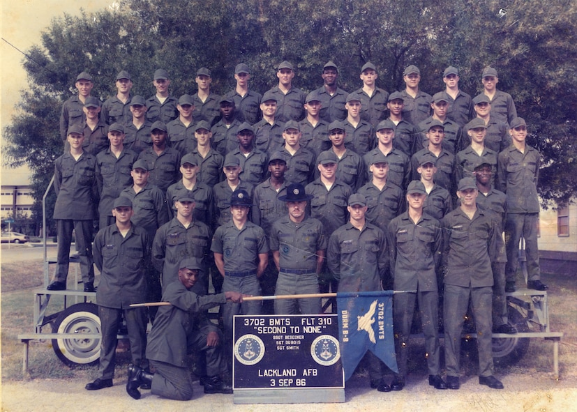 CANNON AIR FORCE BASE, N.M. - Airman Darrell Harris, holding the guidon, and Airman Jarvis Moore, second row from bottom, far right, in their BMT flight photo taken in 1986. Today Master Sgt. Harris and Tech. Sgt. Moore are stationed together again more than 20 years later here. (courtesy photo)