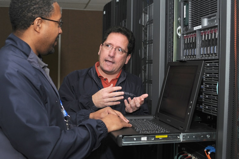 """Patrick Vincent, left, and John Ledet, contractors in the 333rd TRS from General Dynamics Information Technology, set up a """"virtual machine"""" in Stennis Hall for access by students in locations around the world.  (U.S. Air Force photo by Kemberly Groue)"""