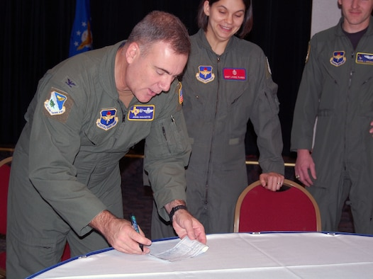 LAUGHLIN AIR FORCE BASE, Texas – Col. John Doucette, 47th Flying Training Wing commander, signs the first check for Laughlin's Air Force Assistance Fund drive at a breakfast fir the campaign at Club XL March 18. The AFAF fundraiser is an annual endeavor to raise money for charitable organizations that provide a helping hand to Air Force members and their families.  The funds raised through AFAF go to organizations such as the Air Force Village Foundation, the Air Force Aid Society, and the General and Mrs. Curtis E. LeMay Foundation. The different organizations then offer financial assistance for a variety of reasons ranging from family emergencies to financial needs. (U.S. Air Force photo by Airman 1st Class Sara Csurilla)
