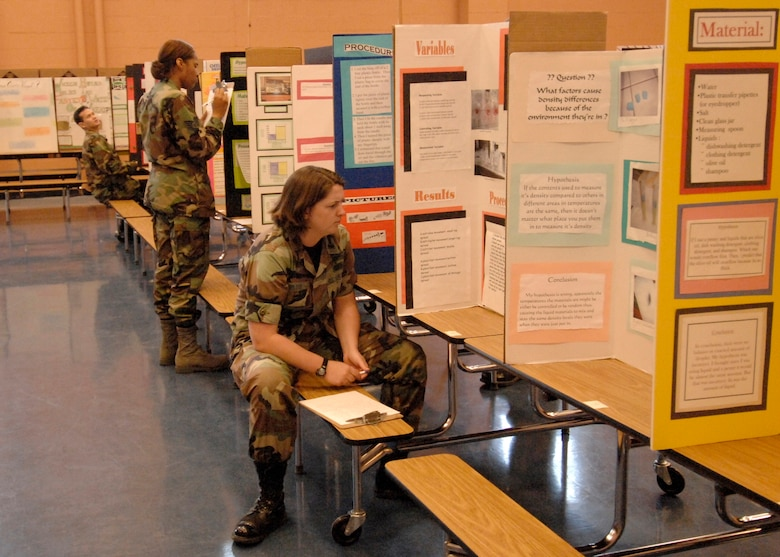 Los Angeles AFB personnel inspect  student science projects at Dana Middle School's annual science fair, March 5. Approximately 10 people volunteered as judges this year. (Photo by Lou Hernandez)