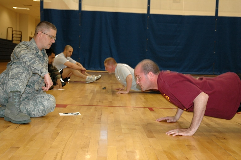 BUCKLEY AIR FORCE BASE, Colo. -- John Dougherty (left), 460th Mission Support Squadron superintendent, encourages Michael Mariner, 2nd Space Warning Squadron, to complete as many push-ups as he can in 10 minutes during the Chief's Push-Up Challenge here March 11. (U.S. Air Force photo by Staff Sgt. Sanjay Allen)