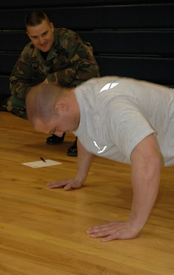 BUCKLEY AIR FORCE BASE, Colo. -- Joseph Soldano, 460th Operations Support Squadron, is hard pressed by Richard Puckett, 460th Mission Support Squadron first sergeant, to complete as many push-ups as possible in 10 minutes during the Chief's Push-Up Challenge here March 11. (U.S. Air Force photo by Staff Sgt. Sanjay Allen)