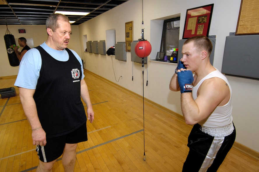 """HANSCOM AFB, Mass. – 2nd Lt. Tim Hunt, State Officer Candidate School Recruitment, Army National Guard, takes instruction from Mr. Leschishin, 66 SVS, during an amateur, Olympic-style boxing class held at the Fitness and Sports Center. Despite professional boxing's dangerous reputation, """"amateur boxing is actually one of the safest contact sports,"""" Mr. Leschishin said. """"It has similar rules and a similar environment to martial arts."""" (U.S. Air Force photo by Mark Wyatt)"""