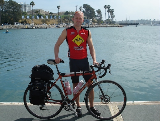Navy Lt. Jeffrey Greene prepares to start his three-month journey in Oceanside, Calif., by dipping his bike tires in the Pacific Ocean. For more on the trip or to follow Lieutenant Greene's progress, visit www.rideforred.com. (Courtesy Photo)