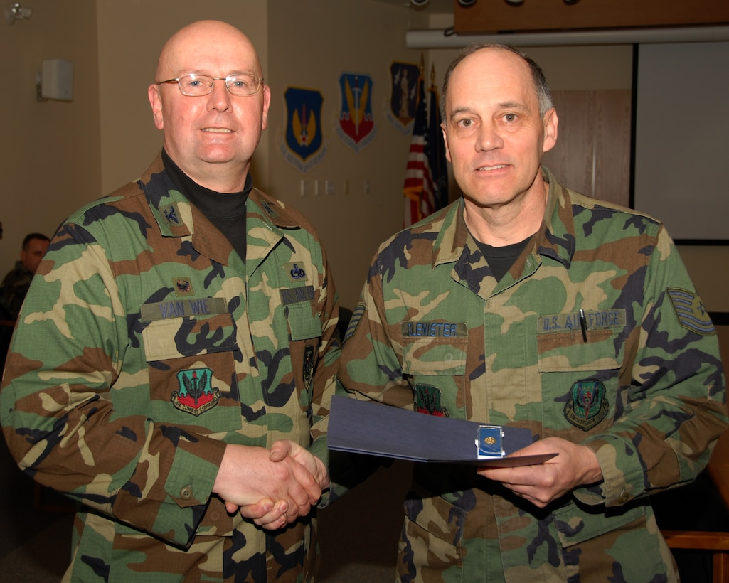 Technical Sergeant Leland R. Glenister of the 174th Fighter Wing, Hancock Field, Syracuse, New York is presented an award for 30 years of military service by Colonel Harvey M. Van Wie, Jr., 174th Support Group Commander on 13 March 2008, during a pre Unit Training Assembly meeting at the 174th Fighter Wing, Headquarters Conference room.  (New York Air National Guard Photo by Staff Sergeant Ben A. Stafford, 174th Public Affairs Office) (Released)