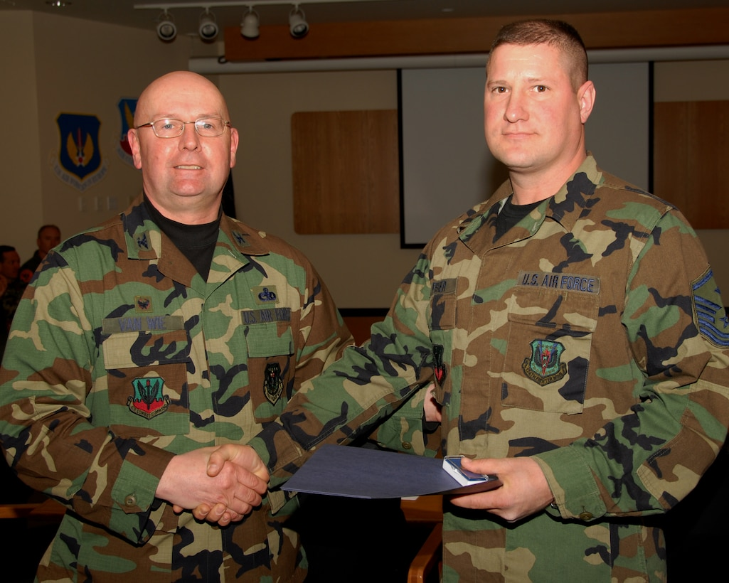 Master Sergeant Dennis Fisher of the 174th Fighter Wing, Hancock Field, Syracuse, New York is presented an award for 15 years of military service by Colonel Harvey M. Van Wie, Jr., 174th Support Group Commander on 13 March 2008, during a pre Unit Training Assembly meeting at the 174th Fighter Wing, Headquarters Conference room.  (New York Air National Guard Photo by Staff Sergeant Ben A. Stafford, 174th Public Affairs Office) (Released)