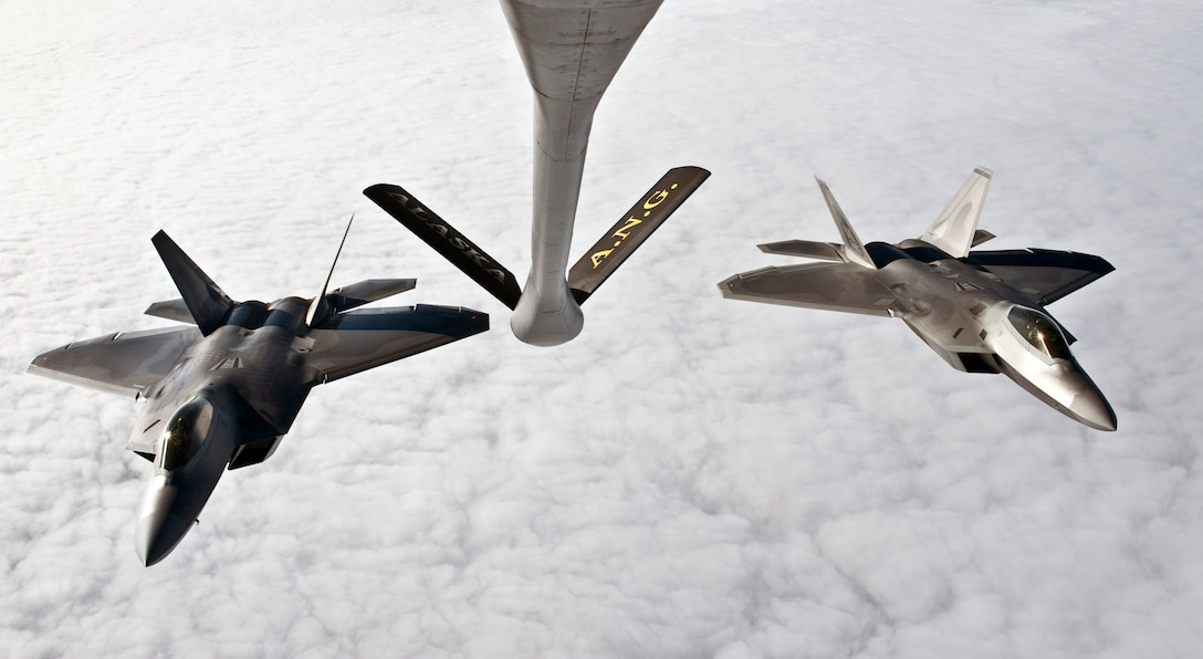 OVER ALASKA -- A KC-135 Stratotanker from the Alaska Air National Guard 168th Air Refueling Wing waits as two F-22 Raptors from the 90th Fighter Squadron at Elmendorf Air Force Base fly in for refueling. With the KC-135's mission of air refueling, the F-22 capabilities can accomplish its mission of global engagement. (U.S. Air Force photo by Airman 1st Class Jonathan Steffen)