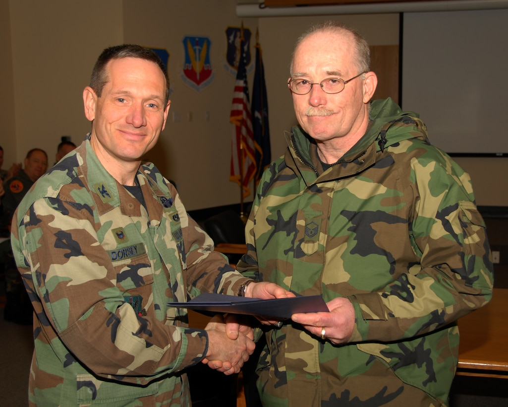Master Sergeant Bruce Oaks of the 174th Fighter Wing, Hancock Field, Syracuse, New York is presented an award for 30 years of military service by Colonel Charles Dorsey, 174th Maintenance Group Commander on 13 March 2008, during a pre Unit Training Assembly meeting at the 174th Fighter Wing, Headquarters Conference room.  (New York Air National Guard Photo by Staff Sergeant Ben A. Stafford, 174th Public Affairs Office) (Released)
