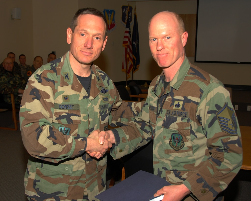 Master Sergeant Mack Lathrop of the 174th Fighter Wing, Hancock Field, Syracuse, New York is presented an award for 25 years of military service by Colonel Charles Dorsey, 174th Maintenance Group Commander on 13 March 2008, during a pre Unit Training Assembly meeting at the 174th Fighter Wing, Headquarters Conference room.  (New York Air National Guard Photo by Staff Sergeant Ben A. Stafford, 174th Public Affairs Office) (Released)