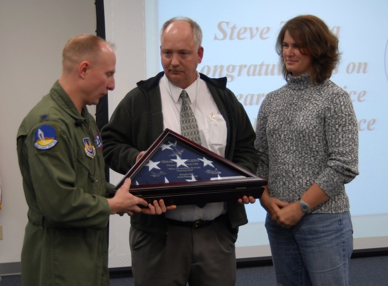 Lt. Col. Carl Schaefer, 445th Flight Test Squadron commander, presents a memento to Steve Zapka, Rohmann Services Inc. project manager, as Bobbi Zapka, aerial photographer and Mr. Zapka's wife, looks on during his 25-year celebration at Edwards. Mr. Zapka has more than 5,000 flying hours as an aerial photographer. (Air Force photo by Airman 1st Class Stacy Sanchez)