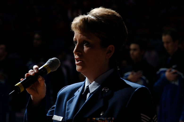 Tech. Sgt. Kristine Keyser, a readiness NCO from the 375th Mission Support Squadron's Airman and Family Readiness Center, sings the national anthem prior to the college basketball semifinals of the Missouri Valley Tournament between the Drake Bulldogs and the Creighton Bluejays held at Scottrade Center, in St. Louis.