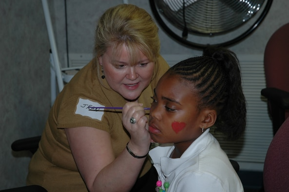 Jean Schmidt, Airman and Family Readiness employee paints Niyiah Roney's face during the Hearts Apart Spring Social March 6.  (U.S. Air Force photo/Airman 1st Class Veronica McMahon)