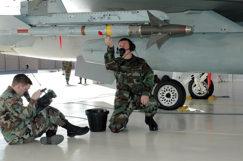 Staff Sgt. Henry Ivy (right), a crew chief with the alert detachment, runs through F-16 launch procedures while Staff Sgt. Pete Blanding, a videographer from Air Combat Command, records the process for training purposes. The film crew from Langley Air Force Base, Va., also captured the inner workings of recovery, pilot responsibilities, crew chief duties and de-arm procedures.
