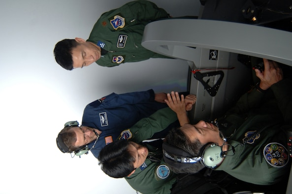 Colonel Yoshiaki Ishii, Japan Air Self Defense Force, prepares for a T-6 simulator Wednesday as Major Mizuho Minamiya, Japan Air Self Defense Force, Major Seiji Yoshida, 14th Operations Group Japanese liaison, and Randy Baareman, Lear Seigler, Inc. Instructor, look on. The JASDEF officers visited CAFB to become better acquainted with the Japanese training taking place here. (U.S. Air Force photo by Senior Airman John Parie)