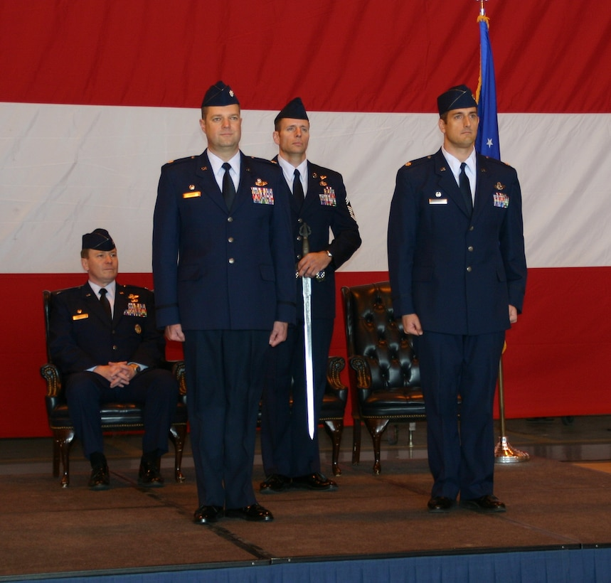 Lt. Col. John T. Russell, 963rd AACS, commander, prepares to pass the traditional Blue Knights' sword over to Lt. Col. Robert M. Haines, who accepted command of the squadron March 7 in a change of command ceremony officiated by Col. Christof P. Cordes, 552nd Operations Group, commander (seated).
