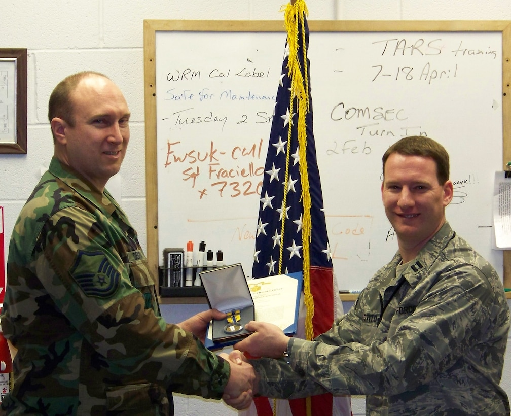 Flightline Avionics Specialist Master Sergeant Duane Degroat receives the Air Force Commendation Medal from Capt. Nick Lotito, AMXS OIC.