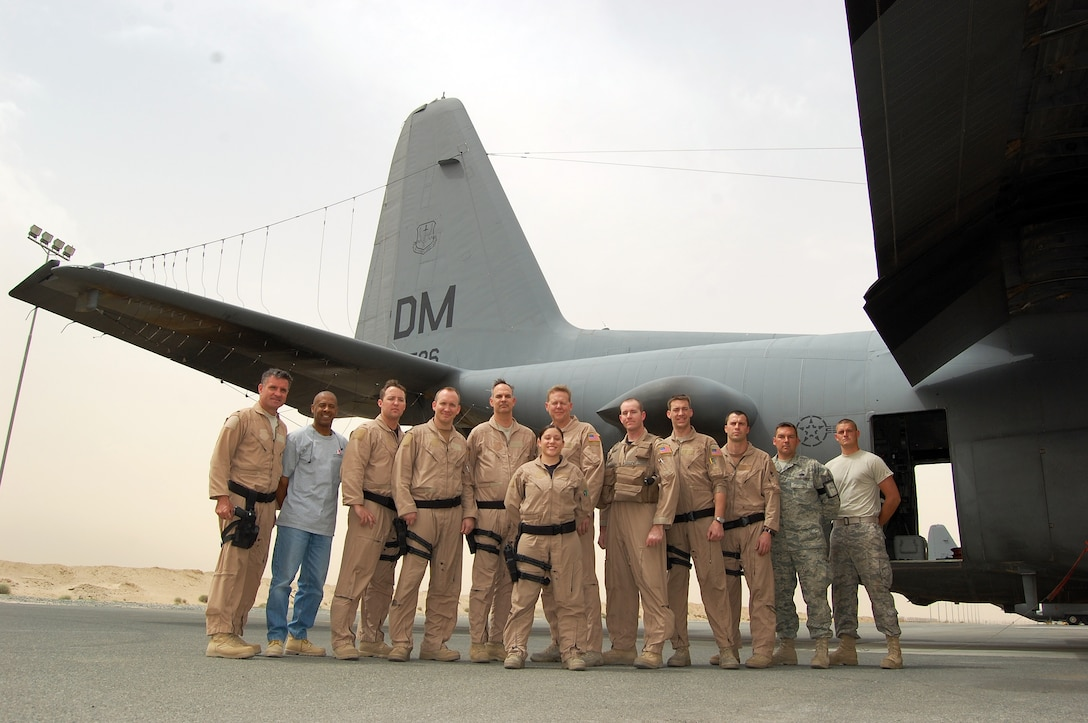 SOUTHWEST ASIA -- Two Airmen and one civilian contractor from the 386th Expeditionary Aircraft Maintenance Squadron pause for a group photo with a nine-person aircrew from the 43rd Expeditionary Electronic Combat Squadron following the completion of a mission on March 18, 2008 at an air base in the Persian Gulf Region. The flying unit's historic 2,276th combat sortie came on the four-year anniversary of the 43rd EECS being consecutively deployed supporting the Global War on Terror. The aircrew and maintenance personnel are deployed from Davis-Monthan Air Force Base, Ariz. (Air Force photo/Tech. Sgt. Michael O'Connor)