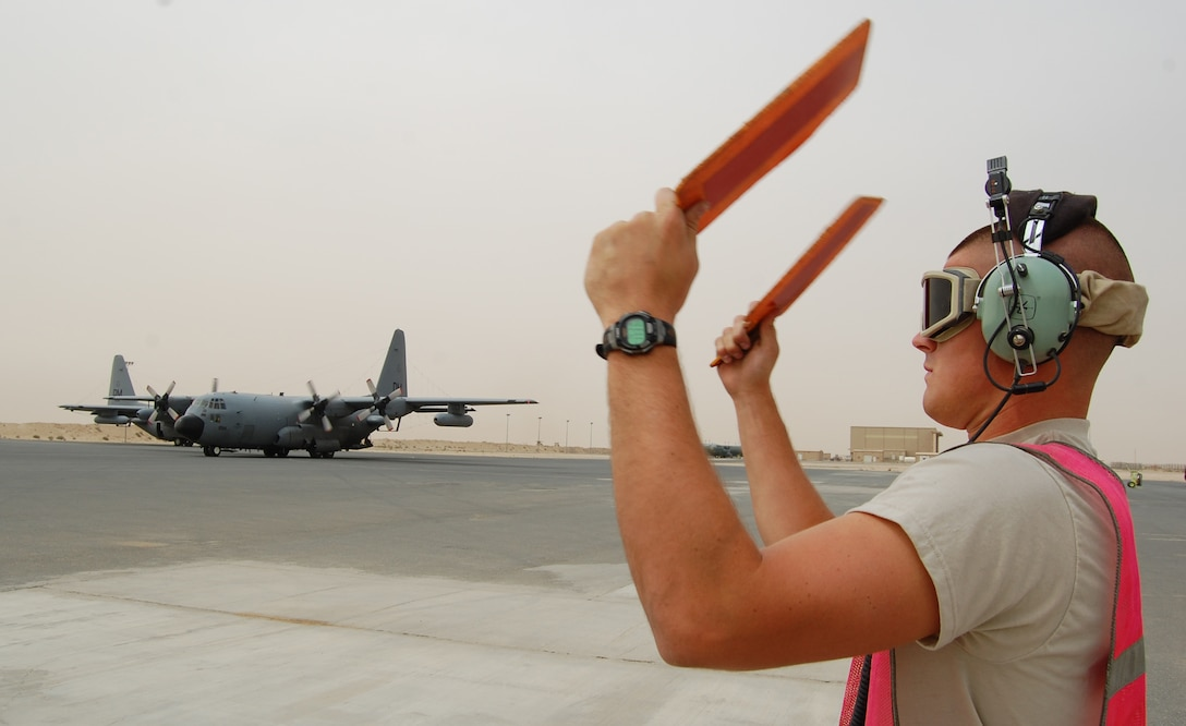 SOUTHWEST ASIA -- Airman Cory Francis, a C-130 crewchief deployed with the 386th Expeditionary Aircraft Maintenance Squadron uses marshalling paddles to direct aircraft commander Capt. Tony Stibral and co-pilot 1st Lt. Corey Hogue returning from a mission March 18, 2008, to their parking spot on the ramp of an air base in the Persian Gulf Region. The pilots and seven other crewmembers from the 43rd Expeditionary Electronic Combat Squadron on board completed the unit's 2,276th combat sortie capping the Arizona-based unit's fourth consecutive year deployed supporting the Global War on Terror. Airman Francis is deployed from the 755th AMXS, and the aircrew members from the 55th Electronic Combat Group out of Davis-Monthan Air Force Base. (Air Force photo/Tech. Sgt. Michael O'Connor)