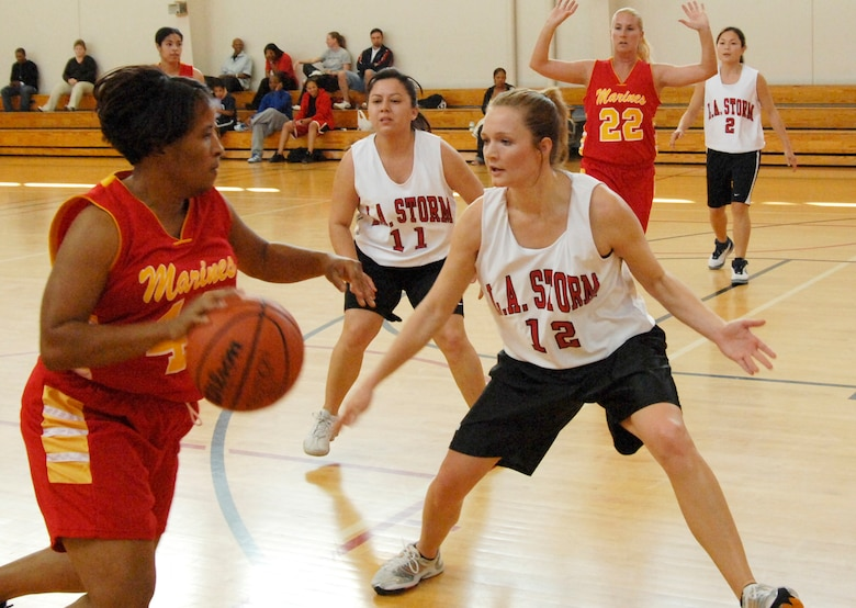 Ayesha DesParte, 61st CS, plays defense against a player from Twenty Nine Palms Marine Corps Base in military basketball league play.  Twenty Nine Palms edged out Los Angeles AFB's Storm 54 to 50. (Photo by Lou Hernandez)