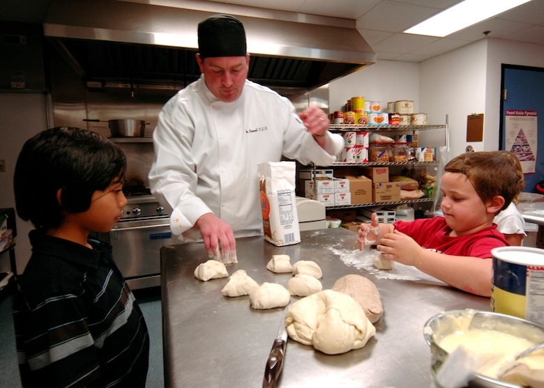 Brian Crowell, husband of Master Sgt Caryl Crowell, teaches kids how to make pizza at a Youth Services cooking class, March 14. (Photo by Lou Hernandez)