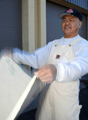 FAIRCHILD AIR FORCE BASE, Wash. – Chito Nacion, 92nd Civil Engineer Squadron painter, applies a drop cloth around the auto hobby shop March 18. The drop cloth ensures paint splatter and spills are kept to a minimum. (U.S. Air Force photo/Staff Sgt. JT May III)