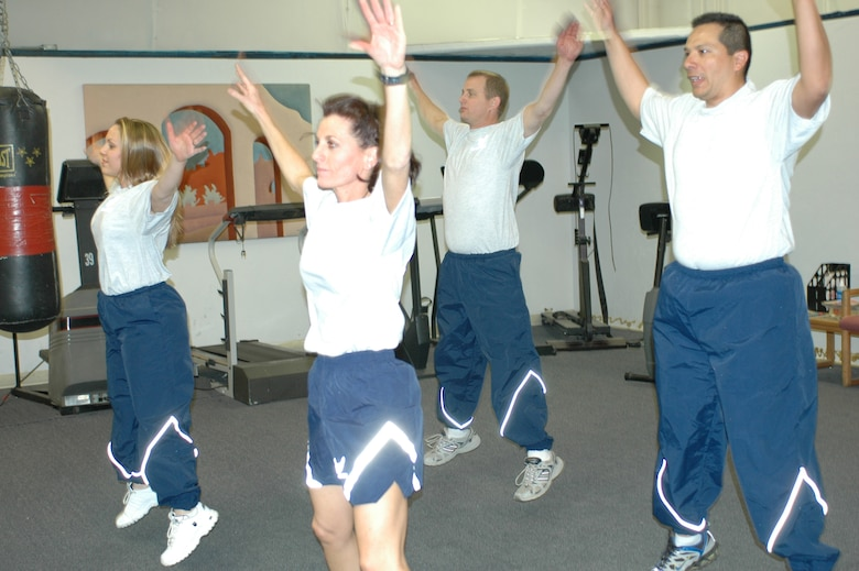Members of the first 9G Force Fitness class continue to apply what they learned weeks after the rigorous program ended. (From left to right) Staff Sgt. Kathleen Branch, Tech. Sgt. Mary Thompson, Tech. Sgt. Mike Coleman and Staff Sgt. Jose Toro warm up with jumping jacks. (Photo by Capt. Gabe Johnson)