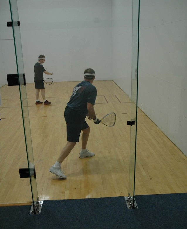 Jerry Kain (background) gets ready to return a serve from a fellow racquetball player during a lunchtime aerobic workout as part of his Largest Loser exercise routine. Mr. Kain plays the game three times a week and supplements on the other days with spinning classes. (U.S. Air Force photo/Valerie Mullett)