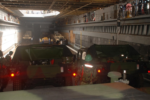 Marines from 4th Landing Support Battalion, 4th Marine Logistics Group, prepare to drive their Humvees from the Improved Navy Lighterage System into the well-deck of the USS Fort McHenry March 21. Aboard the ship, the Marines will prep the vehicles for a humanitarian assistance mission to Monrovia, Liberia as part of West African Training Cruise 2008. The WATC 08 exercise is being held March 17 to April 5 in concert with the ongoing African Partnership Station deployment with a focus on the delivery of humanitarian assistance supplies to various clinics and schools in Monrovia, Liberia from a sea based command.