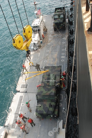 Marines from 4th Landing Support Battalion and Sailors from Amphibious Construction Battalion 2, position a 7-ton Medium Tactical Vehicle as it is moved from the USNS 2nd Lt John Bobo, a maritime prepositioning ship, onto the Improved Navy Lighterage System March 21. The Marines are transferring the equipment in order to evaluate the INLS at sea and to conduct a humanitarian assistance mission in Monrovia, Liberia as part of West African Training Cruise 2008.   The WATC 08 exercise is being held March 17 to April 5 in concert with the ongoing African Partnership Station deployment with a focus on the delivery of humanitarian assistance supplies to various clinics and schools in Monrovia, Liberia from a sea based command.