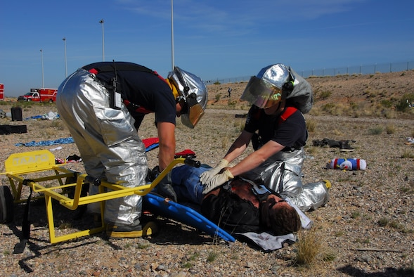 After a simulated plane crash, Senior Airman Bruce Noble (left) and Senior Airman Michael Beller, firefighters assigned to the 162nd Fighter Wing, work together to evacuate a casualty during a major accident response exercise at Tucson International Airport.