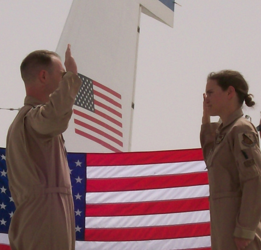 Captain Zachary Stevens, 763rd Expeditionary Reconnaissance Squadron, administers the oath of reenlistment to Senior Airman Kristen Van Slyke, 763rd ERS, on the wing of an RC-135 Rivet Joint aircraft. Airman Van Slyke, along with many other women deployed to the 379th Air Expeditionary Wing, continue the proud heritage of past women aviators and Airmen by their continued dedication and service. Both Captain Stevens and Airman Van Slyke are deployed from Offutt. (Courtesy Photo)