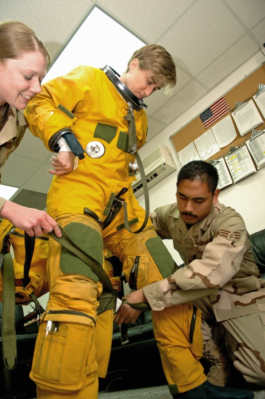 Capt. Heather Fox, a U-2 Dragon Lady pilot with the 99th Expeditionary Reconnaissance Squadron, stands while Senior Airman Roric Ongaco (right) and Staff Sgt. Lisa Tetrick, 99th ERS physiological support division technicians, help attach the torso harness to her suit.  She was preparing to fly a reconnaissance mission March 25 from an air base in Southwest Asia.  Captain Fox is one of only three female U-2 pilots currently serving in the Air Force.  (U.S. Air Force photo/Senior Airman Levi Riendeau)