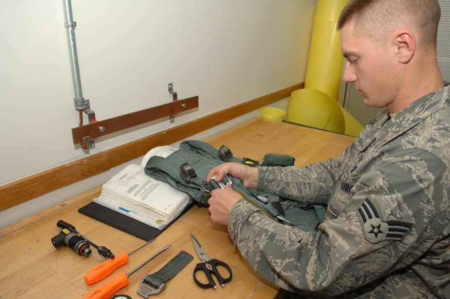 WHITEMAN AIR FORCE BASE, Mo. - Senior Airman Erick Hall, 393rd Bomb Squadron, Aircrew Flight Equipment specialist inspects a PCU-15a harness. Harnesses are inspected every 30 days for damage. Aircrew Flight Equipment Specialist's are capable of making repairs to equipment as needed.  (U.S. Air Force Photo/ Senior Airman Jessica Snow)