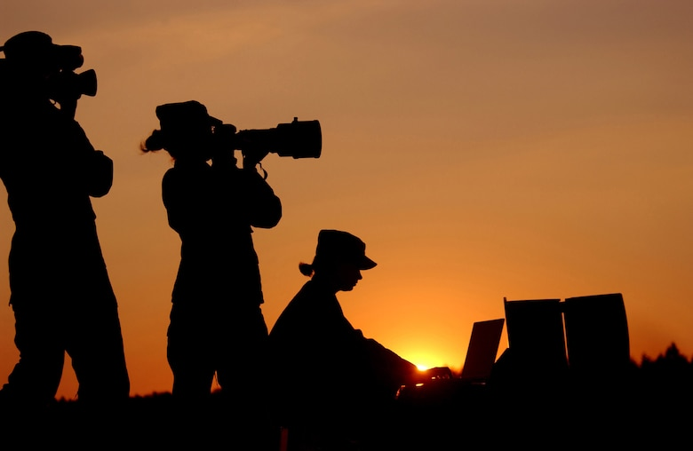 An Air Force videographer (left to right), a still photographer and a graphics specialist are all highlighted by the setting sun. Airmen earned 13 first place awards, nine second place awards and 11 third place awards in the Defense Department 2007 Visual Information Awards contest. (U.S. Air Force photo)