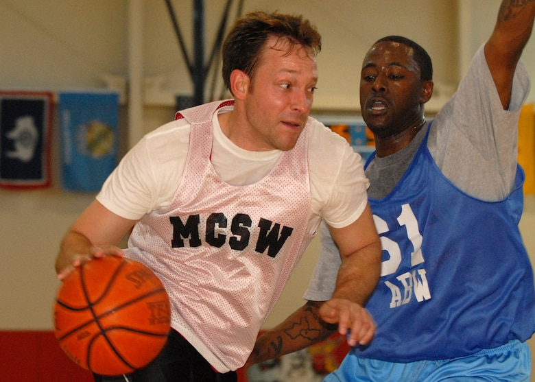 Scott Gribben, MCSW, attempts to dribble around Staff Sgt. Louis Moore, 61st ABW, during the Intramural Basketball championship game, March 27.  The Air Base Wing took the title with a 43 to 42 win. (Photo By Stephen Schester)