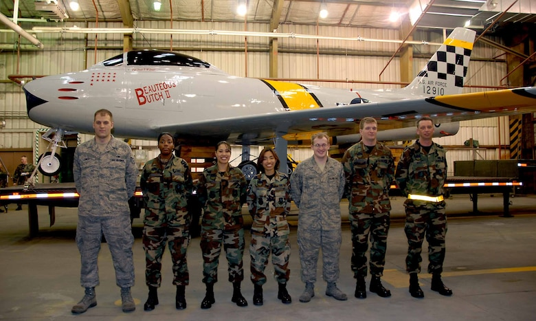 "OSAN AIR BASE, Republic of Korea -- From left to right: Staff Sgt. Robert Jones, Senior Airman Johnetta Gray, Senior Airman Yeleen Neeley, Senior Airman Lisa Caluag, Senior Airman Paul Cotrill, Senior Airman William Crews and Tech. Sgt. Douglas Beals, stand in front of Osan's historic F-86 Sabre static display aircraft after its restoration and a new ""checkertail"" paint scheme. The aircraft will be displayed in front of Base Operations. All Airmen are aircraft structural technicians from the 51st Maintenance Squadron. (U.S. Air Force photo/Senior Master Sgt. Marvin Krause)"