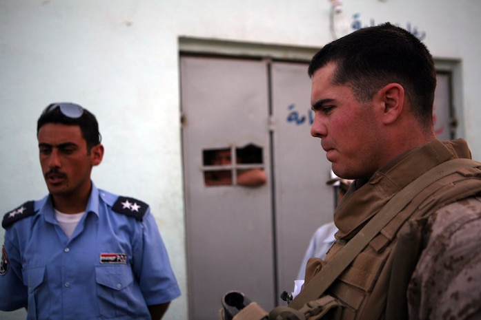 Second Lt. Mike A. Jevons, 24, an infantry officer from Manhattan, Kan., assigned to 3rd Battalion, 4th Marine Regiment, Regimental Combat Team 5, speaks with Iraqi policemen about recent activity in Hit. Marines took a tour of the Iraqi Police station, which included the holding facilities of criminals. Marines and policemen discussed conducting patrols together in the near future.