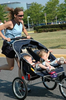 "At the summer 2006 Tim Harmon 5K, in Fairfax, Va., Senior Master Sgt. Jennifer Burg teamed up with her twin daughters, Maddy and Kaylee, to win the Baby Jogger Division. ""As a single active duty mother of twins, training is quite a challenge,"" she says. ""I find unique ways to incorporate them into the training I do during 'girl' time.  They hop in the jogger, cover up with blankets, and find ways to entertain themselves."" (Photo courtesy of Senior Master Sgt. Jennifer Burg.)"
