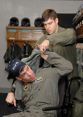 Pilot for a Day, Alan Wakefield II, tries on a g-suit with the help of Capt Jackson Whiting, 95th Fighter Squadron pilot, March 28. Before heading out to see the practice air show on Tyndall's flightline, Wakefield paired with the pilot to experience life as an Air Force aviator to include a simulator ride and tours of aircraft maintenance facilities. (U.S. Air Force photo by Isaac Gibson)